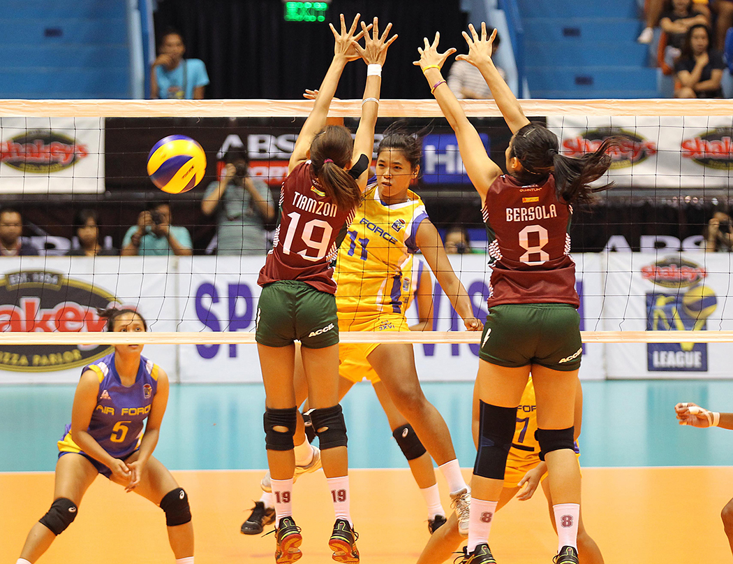Judy Ann Caballejo of Air Force (11) hammers in a kill against UP's Nicole Tiamzon (19) and Katherine Bersola during their Shakey's V-League showdown.