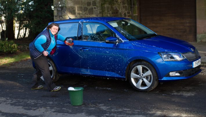 Photo of a woman cleaning a car.
