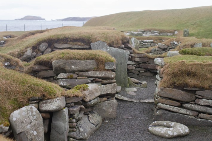 A photo of Jarlshof, Shetland. Showing the layers of stones with grass on top. Pathways which would have formed part of the house