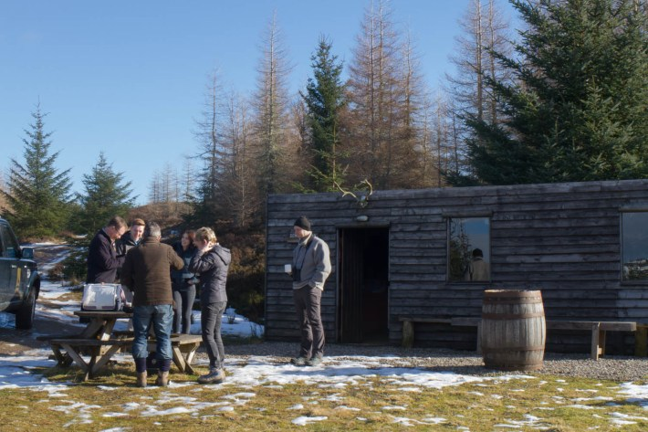 Highland Safaris, Perthshire. A group of people outside a wooden bothy drinking a hot drink during a tour. Snow on the ground and the sky is blue.