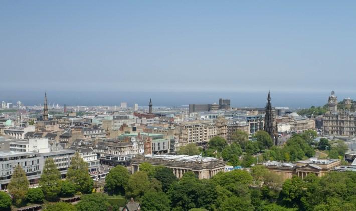 Roof tops across Edinburgh city. Blue sky, tree tops, tall spires