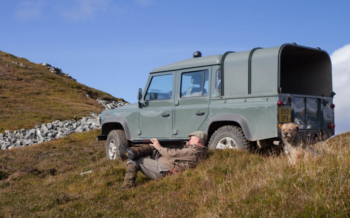 Glenesk Wildlife tours. A man lay beside his LandRover 4x4 looking through a telescope for wildlife