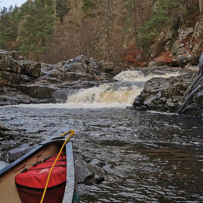 Photo of the Linn of Tummel waterfalls. In the foreground is the front of a canoe