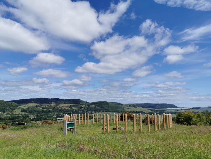 Image of blue sky with whispy white clouds and a circle of wooden poles in the ground at Moncrieffe Hill, Perthshire