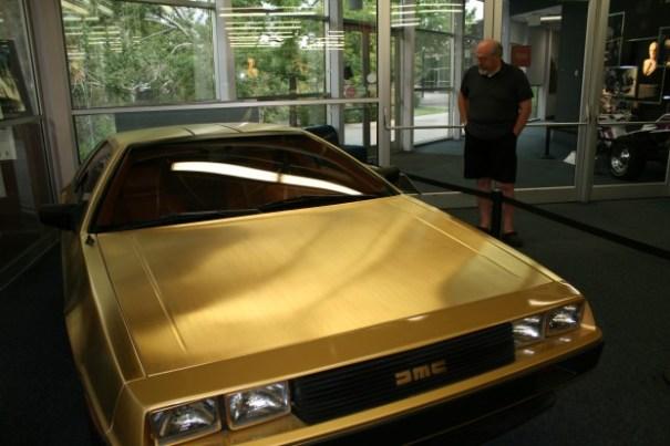Grumpy old man looking at 24K gold plated Delorean.