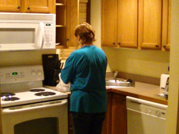 Pretty woman in the kitchen, putting stuff away.