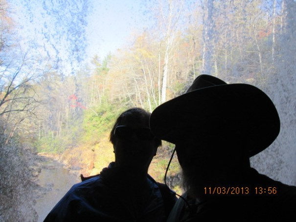 Grumpy old man and pretty woman under the falls taking a selfie.