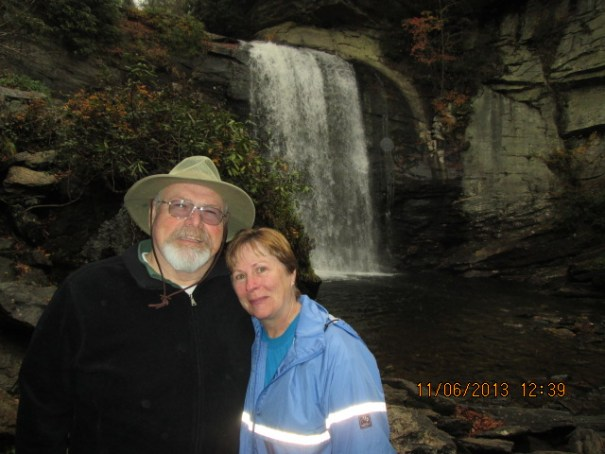 Grumpy old man with a pretty woman in front of Looking Glass Falls.
