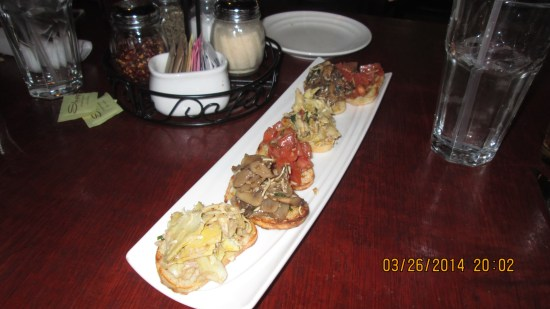 Bruchetta appetizer with artichoke hearts, tomatoes and mushrooms.