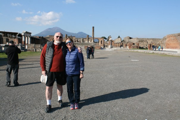 Grumpy and pretty woman with Mount Vesuvius in the distance.