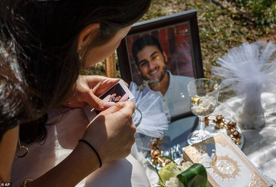 Baluch is seen clutching a photo of her and Sharifi at his grave, which has been covered with flowers and mementos as his headstone isn't finished yet