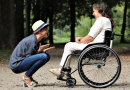 person wearing a white hat and blue jeans is crouching in front of a person wearing all white in a wheelchair. Both people are laughing together in a forest
