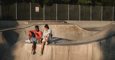 Two young men sitting with skateboards in skate park