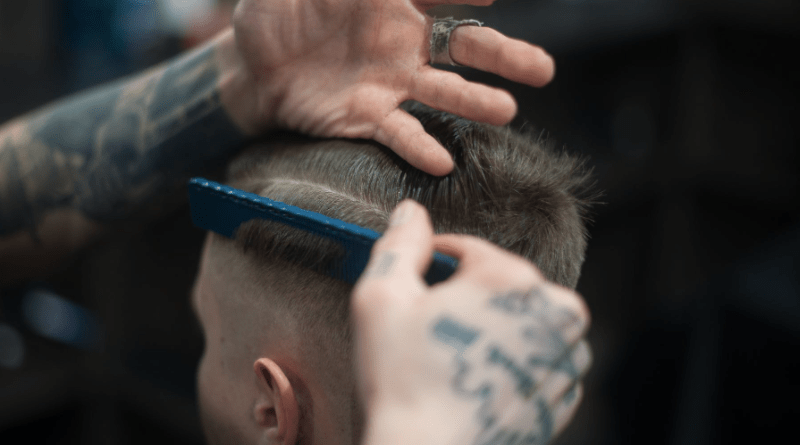 A haircut taking place in a barbers, head of the client and hands of the barber using a comb on the client's hair