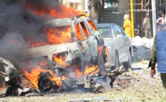 Somali soldiers pass near the burning wreckage of a car bomb in Mogadishu Somalia, Saturday, Oct. 1, 2016. A Somali police officer says a car bomb struck the entrance of a restaurant in the Somali capital Saturday, killing two people. Capt. Mohamed Hussein said that the blast occurred as Blue Sky restaurant which is close to the presidential palace was packed with diners. (AP Photo/Farah Abdi Warsameh)