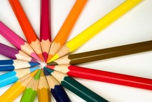 Stock photograph of brightly colored pencils forming a symmetric pattern.