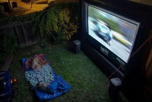 kids enjoying a backyard party rental with blow up movie screen