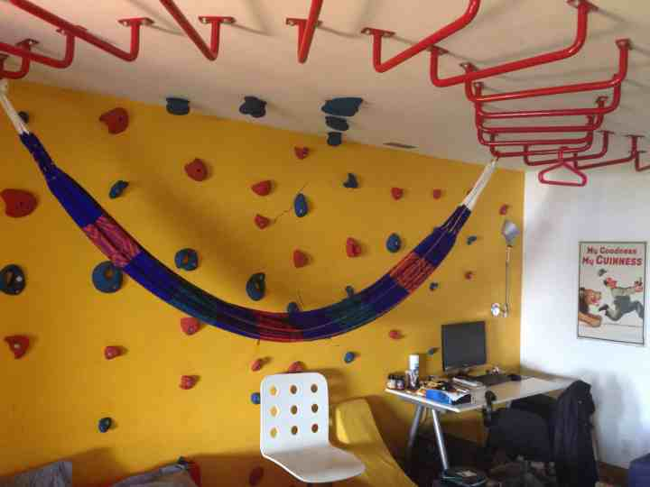 Totally cool big kids bedroom with climbing wall and monkey bar ceiling. Check out more genius indoor climbing ideas here.