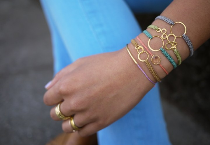 several macrame bracelets in various colors on a person's wrist