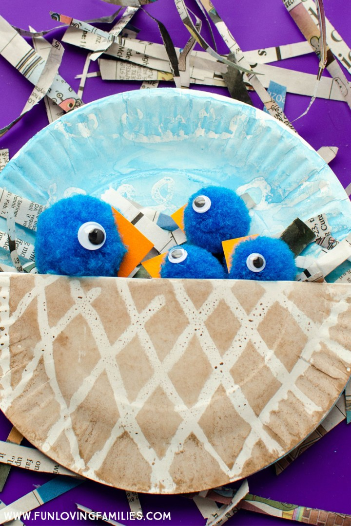 completed paper plate bird nest craft with blue birds
