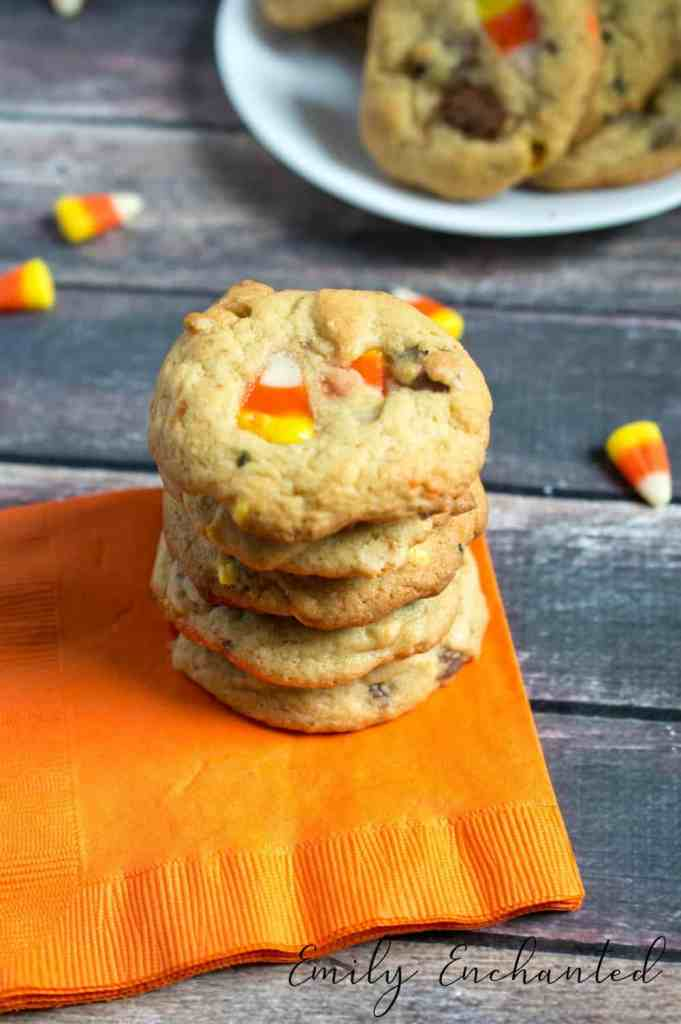 stack of candy corn cookies on orange napkin with plate of cookies in the background