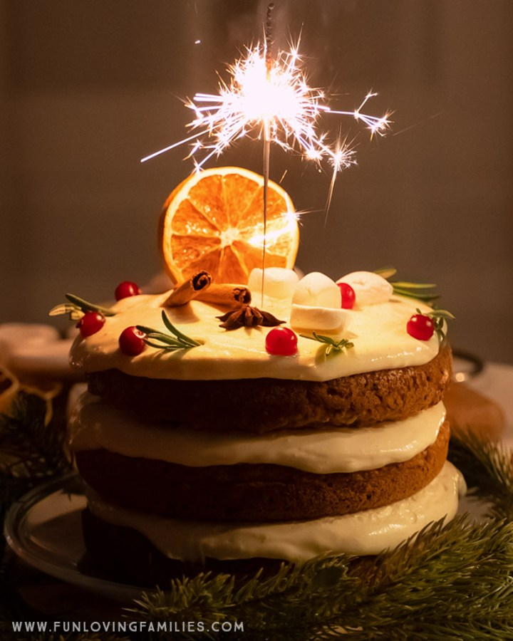 festive Christmas cake with sparkler on a table with fir tree branches