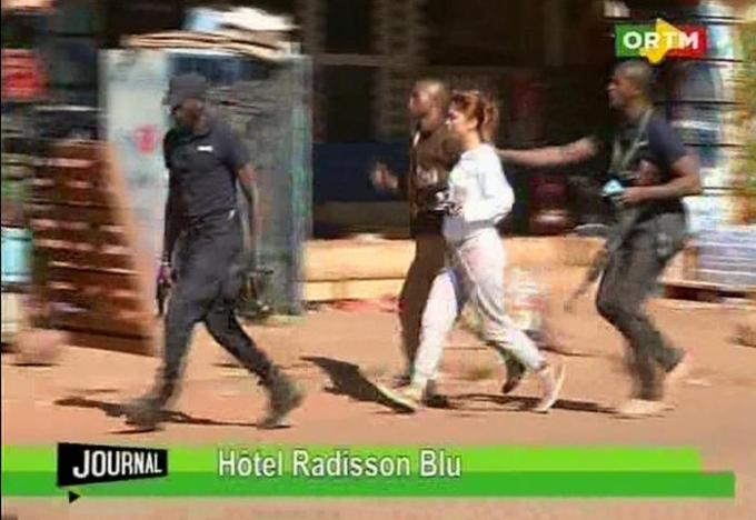 "In this TV image taken from Mali TV ORTM, a woman is led away by security personnel from the Radisson Blu Hotel  hotel in Bamako, Mali, Friday Nov. 20, 2015.  Men shouting ""God is great"" and armed with guns and throwing grenades stormed into the Radisson Blu Hotel in Mali's capital Friday morning. (Mali TV ORTM,  AP) MALI OUT"