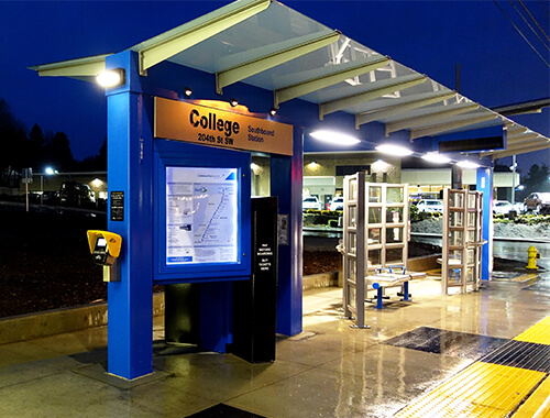 waiting shelter with a covered canopy over ticket machine.