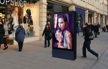 "Double sided 75"" Digital 6 sheet outdoor display on a side walk next to a retail shop."