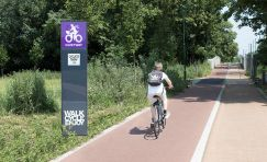 Digital cycle counter totem next to a cycle path & someone riding a bicycle.