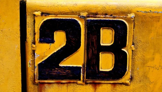 """A yellow sign has black lettering that reads """"2B"""""""