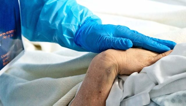 A doctor wearing blue gloves and blue PPE touches a patient's hand