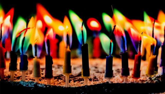Colorful candles burning on a cake in the dark