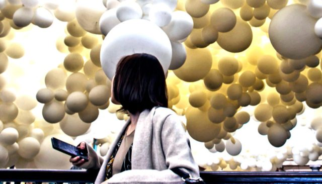 A woman looks over her shoulder to see huge yellow and white balloons filling the sky behind her