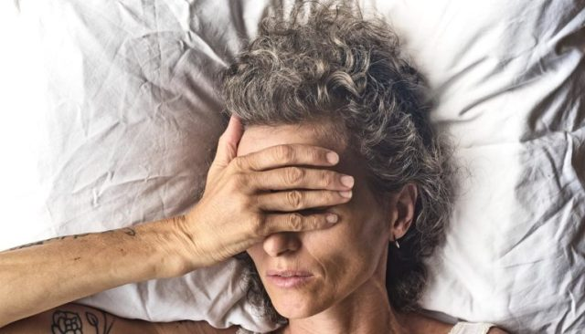 A woman laying on a white pillow puts her hand over her face