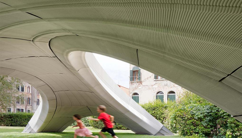 Kids run under the bridge, showing the grooved, curved concrete underneath