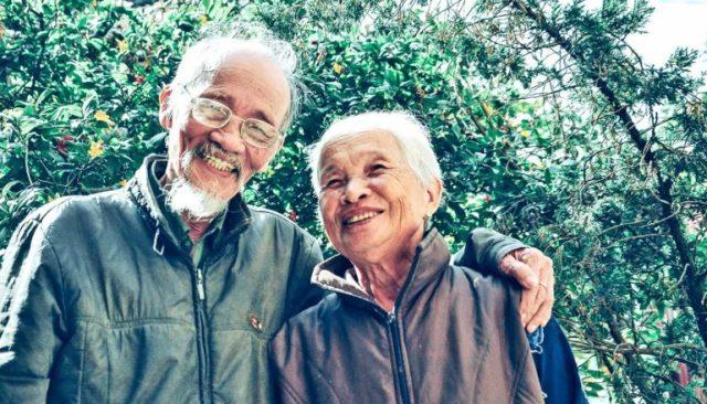 Een ouder stel lacht samen voor groene struiken