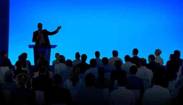 silhouetscène van persoon die op het podium spreekt voor zittende menigte