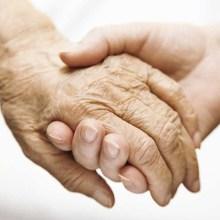 An elderly couple holding hands.