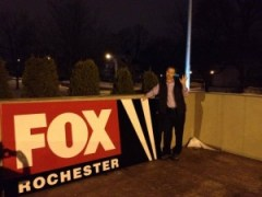 WROC's Scott Hetsko poses with the WUHF sign after it was removed from WROC's building in December