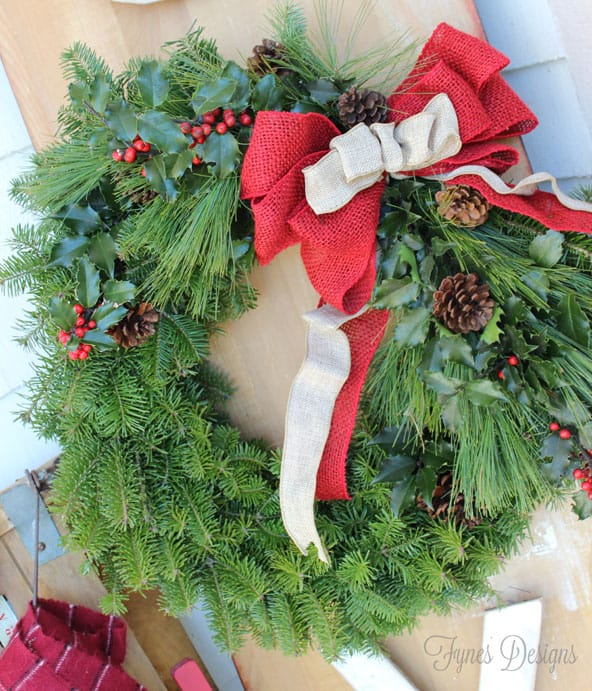 traditional balsam wreath with pine, holly, pinecones with a coloured burlap bow |Joy Sign by popular DIY Canada blog: image of a Christmas wreath with red and neutral burlap ribbons, holly sprigs, and pinecones.