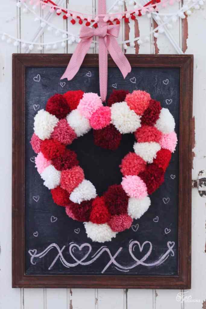 How to make a heart shaped wreath for only $2, a craft featured by top US craft blog, FYNES DESIGNS |Heart Shaped Wreath by popular Canada DIY blog, Fynes Designs: image of a pink, white and red heart shaped pom pom wreath.