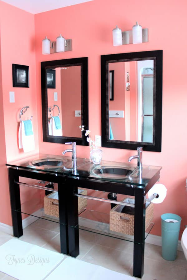 Cheap bathroom makeover #homedepot #voiceofcolor | Bathroom Makeover Ideas and Inspiration by popular Virginia life and style blog, Fynes Designs: image of a bathroom with coral pink walls, black framed mirrors, and black double vanity with glass top.