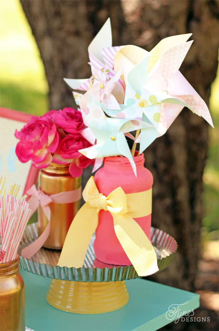 Cute paper pinwheels make a cheap table decoration in a painted pasta sauce jar