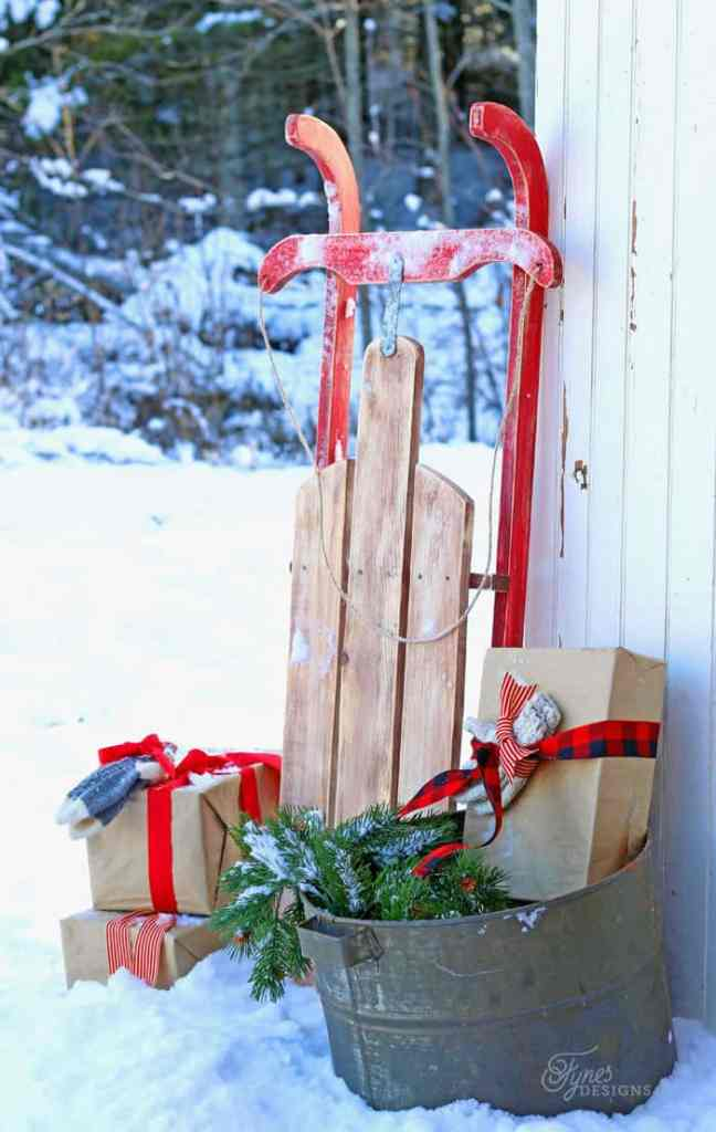 $10 DIY Wooden Sled Tutorial featured by top US craft blog, Fynes Designs | DIY Wooden Sled by popular Canada DIY blog, Fynes Designs: image of a vintage inspired DIY wooden sled surrounded by some brown package wrapped in brown paper and red ribbons.