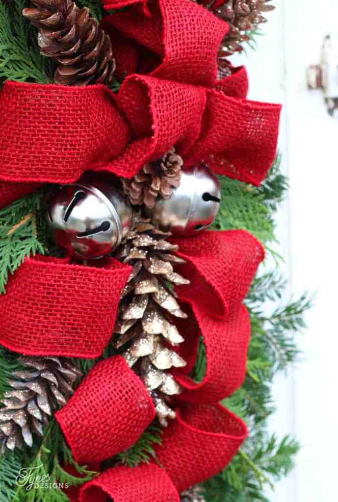 Easy to follow instructions for how to make a Christmas swag wreath |Swag Wreath by popular Canada DIY blog, Fynes Designs: image of a swag wreath with red burlap ribbon, pinecones and silver sleigh bells.