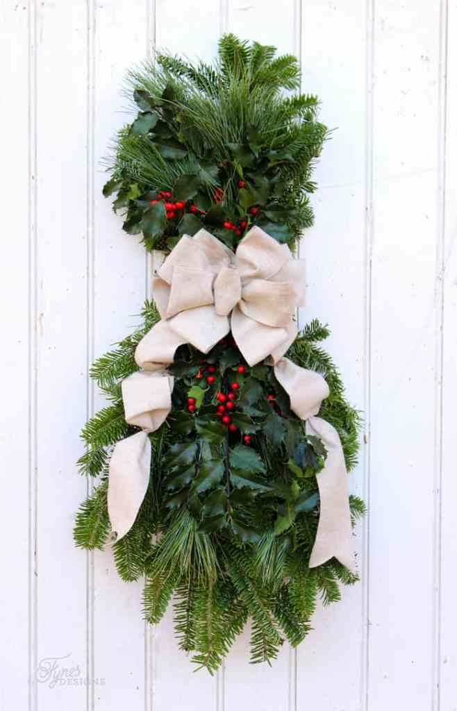 Easy to follow step by step instructions for making a natural holiday swag | Swag Wreath by popular Canada DIY blog, Fynes Designs: image of a swag wreath with a cream ribbon, holly, and pine boughs.