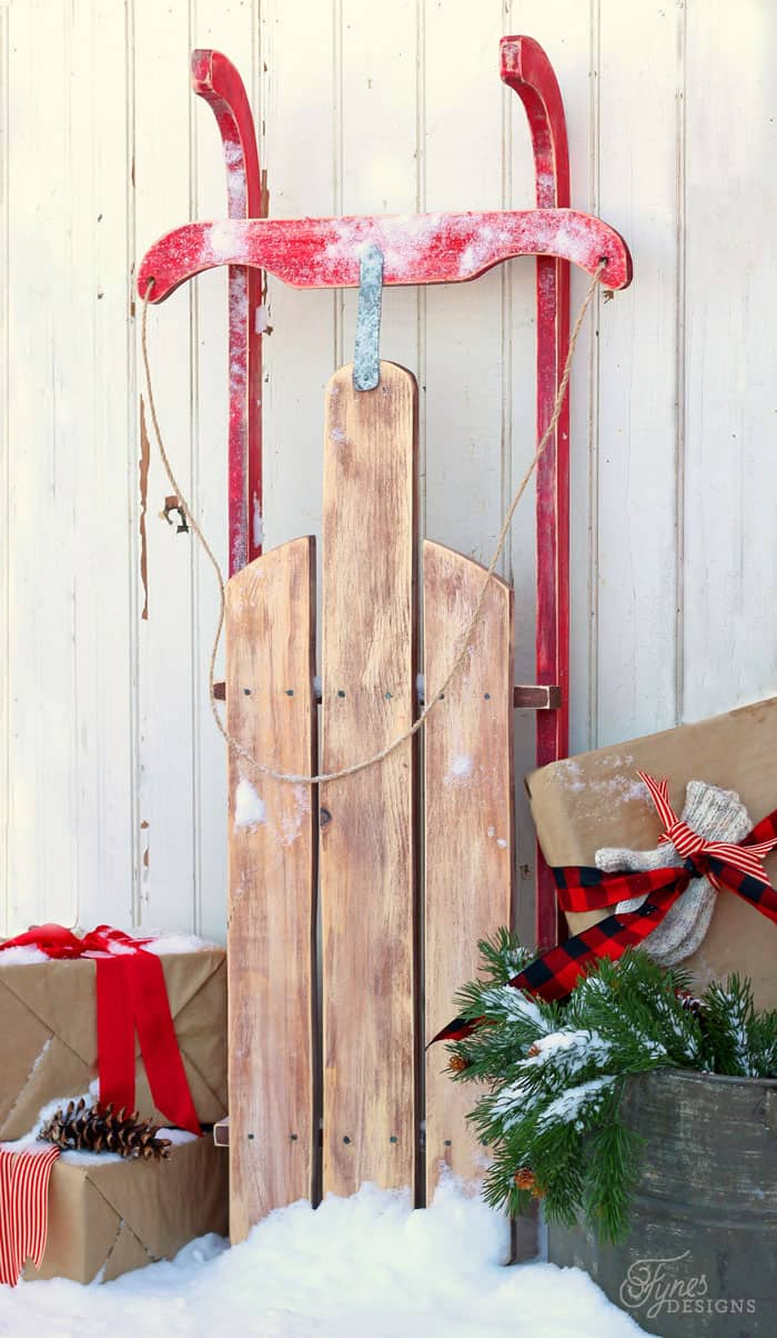 $10 DIY Wooden Sled Tutorial featured by top US craft blog, Fynes Designs: Easy to build $10 Vintage Sled |DIY Wooden Sled by popular Canada DIY blog, Fynes Designs: image of a vintage inspired DIY wooden sled surrounded by some brown package wrapped in brown paper and red ribbons.