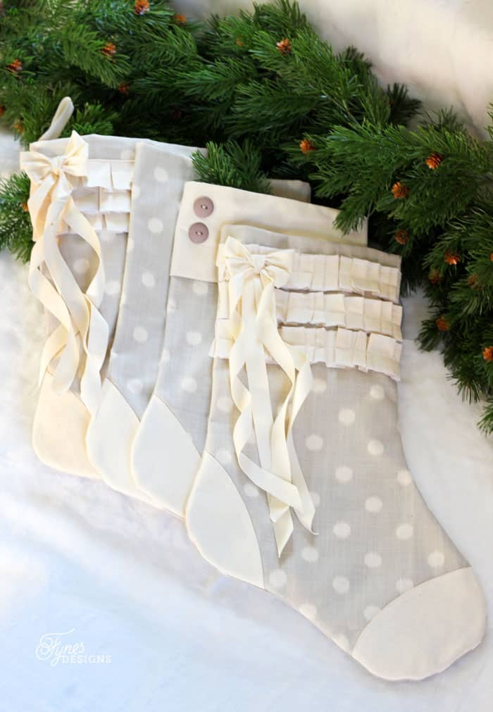Make your own handmade Christmas stockings with this easy tutorial and free pattern.  DIY Personalized Christmas Stockings by popular Canada DIY blog, Fynes Designs: image of grey and white stockings laying next to some green pine garland.