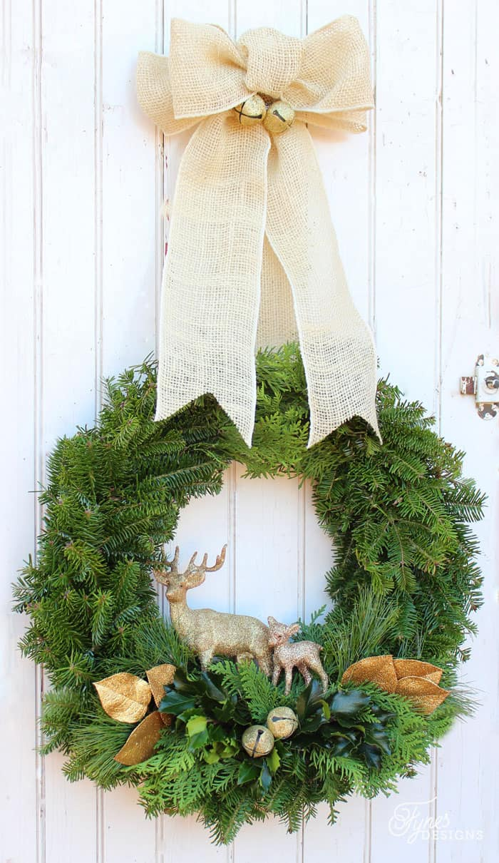 Learn to make a handmade natural Christmas wreath | Christmas Wreath by popular Canada DIY blog, Fynes Designs: image of a natural Christmas wreath with a burlap bow, gold jingle bells, faux gold leaves, and gold deer.